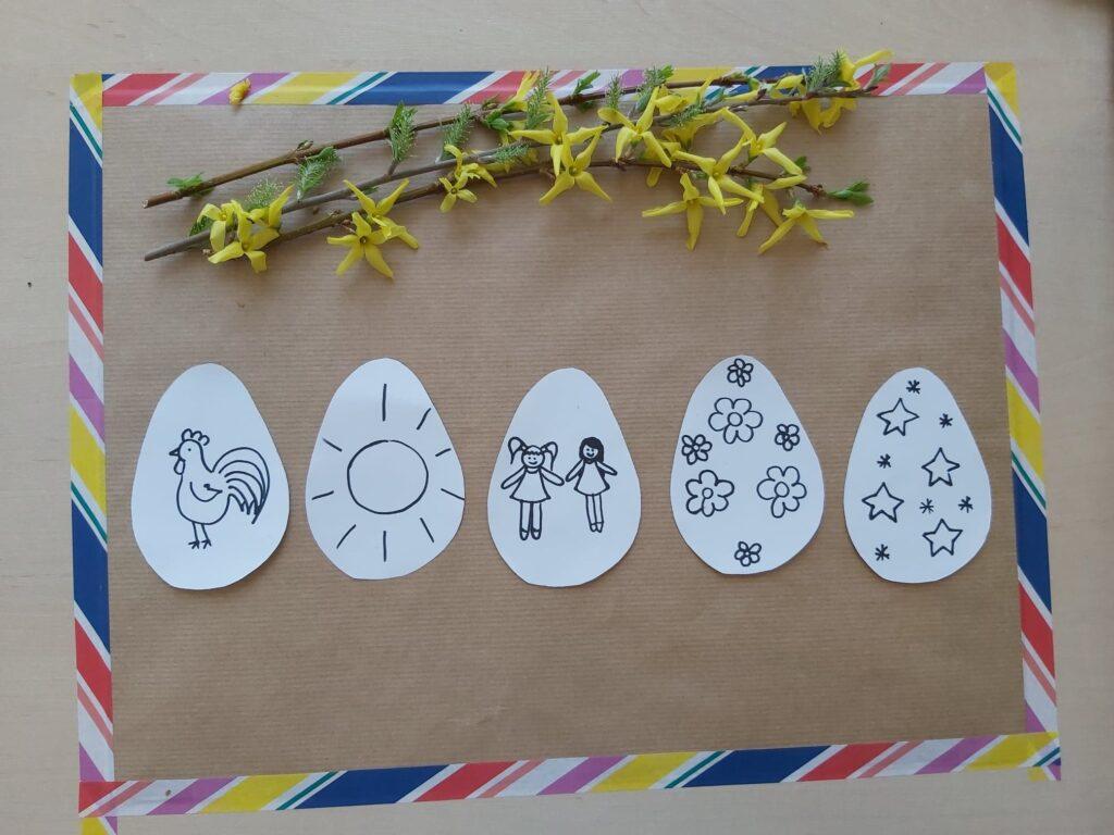 Na kartce leżą papierowe jajka z rysunkami koguta, słońca, laleczek, kwiatków, gwiazdek