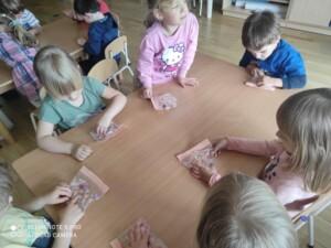 Dzieci przy stołach badają zmysłem dotyku woreczki strunowe z żelem w środku.
