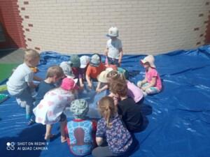 Dzieci siedząc w kole wyciągają ręce by sprawdzić temperaturę wody.