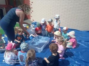 Dzieci siedzą w kole, na środku jest duży pojemnik, nauczyciel wlewa do niego wiaderko wody.