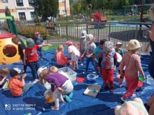 Cała grupa bawi się na macie gdzie są ustawione kąciki z wodą, makaronem, kolorowym ryżem oraz barwnikami.