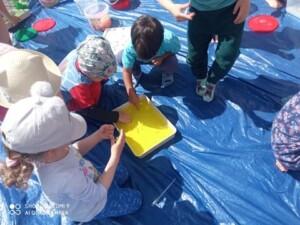 Dzieci bawią się żółtą galaretką w pojemniku.