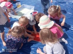 Dzieci bawią się czerwoną galaretką w pojemniku.