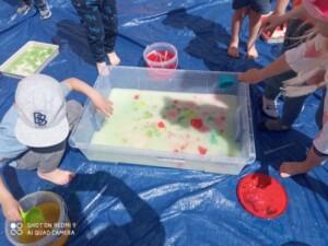 Kilkoro dzieci miesza w dużym pojemniku wodę, mąkę, galaretkę oraz kolorowe barwniki spożywcze.