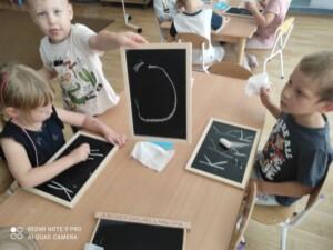 Dzieci przy stole piszą na tabliczkach kredą.