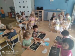Grupa dzieci przy stołach pisze na tabliczkach kredą.