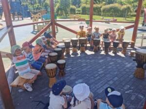 Warsztaty bębniarskie. Dzieci słuchają zasad gry na bębnach.
