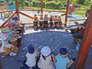 Warsztaty bębniarskie. Dzieci grają na bębnach.