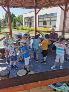 Warsztaty bębniarskie. Dzieci tańczą do muzyki